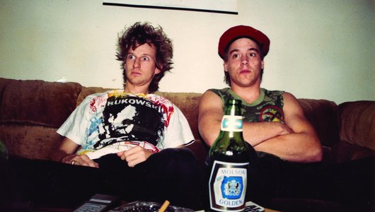 Two men sitting on a couch, with a beer bottle in the foreground.
